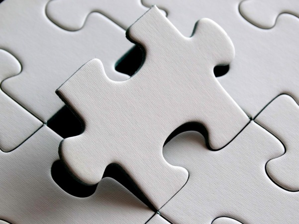 white puzzle piece being placed into puzzle