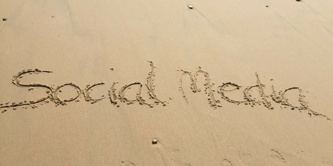The words Social Media written in the sand at a beach